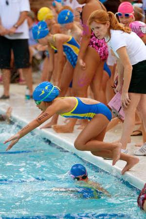 Lawrenceville, GA, Verenigde Staten - 14 juni: Een vrouwelijke jeugd zwemmer duikt in zwembad om haar been van een estafette zwemmen tijdens een buurt zwemmen ontmoeten tussen drie duik teams.