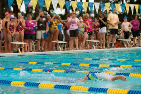 Lawrenceville, GA, USA - June 14:  A female youth swimmer does backstroke as spectators look on, during a neighborhood swim meet between three swim teams.