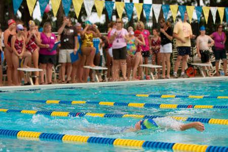 Lawrenceville, GA, Verenigde Staten - 14 juni: Een vrouwelijke jeugd zwemmer doet rugslag als toeschouwers kijken, tijdens een buurt zwemwedstrijd tussen drie duik teams.