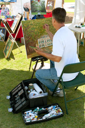 Suwanee, GA, USA - May 19, 2012:  An artist paints on canvas in his exhibitor booth at the Arts In The Park Festival, an outdoor event held at Suwanee Town Park. Editorial