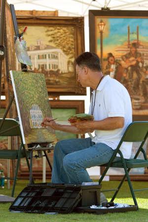 expositor: Suwanee, GA, EE.UU. - 19 de mayo de 2012: Un artista pinta sobre tela no identificados en su stand expositor en las artes en el Festival Park, un evento al aire libre celebrada en Ciudad Suwanee Park.