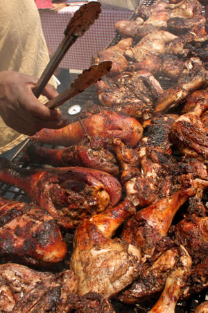 Large amounts of chicken barbeque on a grill at an outdoor arts festival.  photo