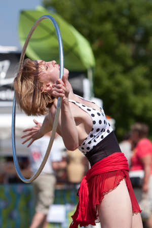 Suwanee, GA, USA - May 19, 2012:  A female circus performer does the hula hoop, performing for patrons attending the Arts In The Park spring festival at Suwanee Town Park in downtown Suwanee.  The performers are part of The Imperial OPA Circus, a local ci