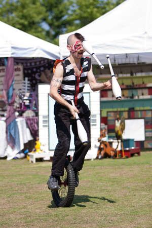 Suwanee, GA, USA - May 19, 2012:  A male circus performer juggles pins riding a unicycle while  performing for patrons attending the Arts In The Park spring festival at Suwanee Town Park. The performers are part of the Imperial OPA Circus, a local circus