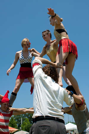 piramide humana: Suwanee, GA, EE.UU. - 19 de mayo de 2012: Un grupo de desconocidos artistas de circo construye una pir�mide humana, en el desempe�o para los clientes que asisten a las artes en la fiesta de la primavera en el Parque de la ciudad Parque Suwanee en Suwanee centro.
