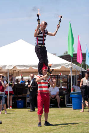 Suwanee, GA, USA - May 19, 2012:  Two male circus performers entertain the crowd as they juggle flaming batons while performing at Arts In The Park, a spring festival held at Suwanee Town Park.  The perfomers represent The Imperial OPA Circus, a local tro