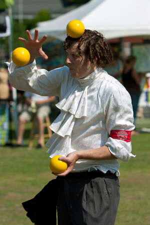 tosses: Suwanee, GA, USA - May 19, 2012:  A juggler tosses bright yellow balls in the air, as he performs for patrons attending the Arts In The Park spring festival at Suwanee Town Park in downtown Suwanee.  The juggler was part of the Imperial OPA Circus, a loca Editorial