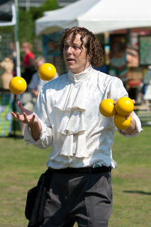 tosses: Suwanee, GA, USA - May 19, 2012:  A juggler tosses bright yellow balls in the air, as he performs for patrons attending the Arts In The Park spring festival at Town Center Park in downtown Suwanee.  The juggler was part of the Imperial OPA Circus, a local