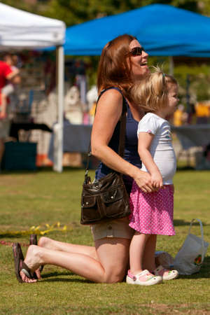 festival moment: Suwanee, GA, USA - May 19, 2012:  A mother and her young daughter share a special moment while listening to a band play at the Arts In The Park spring festival in downtown Suwanee.