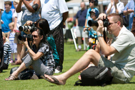 Suwanee, GA, USA - May 19, 2012:  Several people in the crowd take photos with DSLRs and long lenses, as a performance goes on at the Arts In The Park arts festival held at Suwanee Town Park.