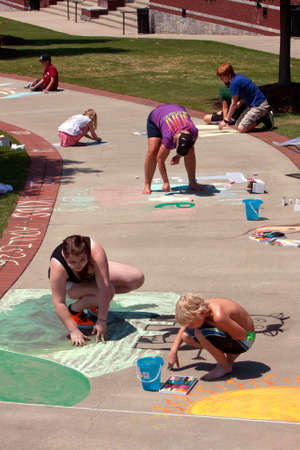 Suwanee, GA, USA - May 19, 2012:  Unidentified festival goers draw on the sidewalk with chalk at Arts In The Park, an outdoor arts festival held at Suwanee Town Park.  Chalk art was one of the active projects going on at the festival. Editorial