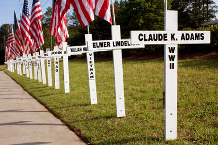 Duluth, GA, USA - May 19, 2012:  Crosses marked with the names of Duluths fallen soldiers and the wars they died in, line a sidewalk adjacent to Georgia State Road 120 in Duluth.  The Duluth community puts out the crosses each year to commemmorate Memori
