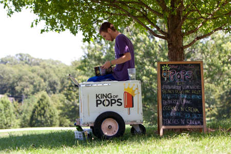 Atlanta, GA, USA - July 28, 2012:  An unidentified ice cream vendor reads a book to pass the time as he waits for customers in an Atlanta public park.  The vendor was waiting for an organized water gun fight to start.