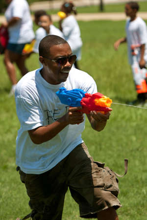 Atlanta, GA, USA - July 28, 2012:  An unidentified man participates in a group water gun battle called the Fight4Atlanta, a fun squirt gun fight between dozens of local residents at Atlanta's Freedom Park.  The event was free and open to the public. Stock Photo - 15621440