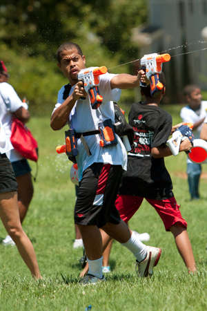 Atlanta, GA, USA - July 28, 2012:  An unidentified man participates in a group water gun battle called the Fight4Atlanta, a fun water gun fight between dozens of local residents at Atlanta's Freedom Park.  The event was free and open to the public. Stock Photo - 15621436