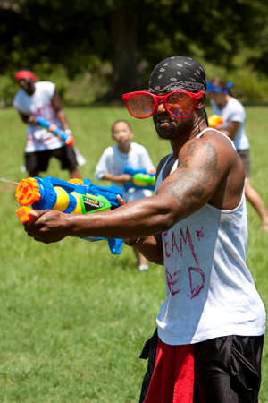 Atlanta, GA, USA - July 28, 2012:  An unidentified young man participates in a huge water gun battle called the Fight4Atlanta, a fun water gun fight between dozens of local residents at Atlanta's Freedom Park.  The event was free and open to the public. Stock Photo - 15621448