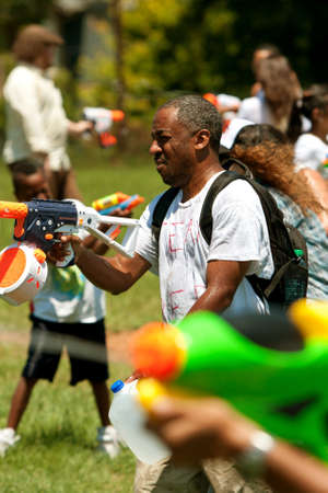 Atlanta, GA, USA - July 28, 2012:  Several unidentified people participate in a huge water gun battle called the Fight4Atlanta, a fun water gun fight between dozens of local residents at Atlanta's Freedom Park.  The event was free and open to the public. Stock Photo - 15621442