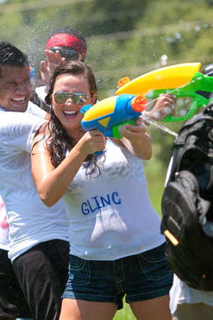 dozens: Atlanta, GA, USA - July 28, 2012:  Unidentified people participate in a group water gun battle called the Fight4Atlanta, a fun squirt gun fight between dozens of local residents at Atlantas Freedom Park.  The event was free and open to the public.