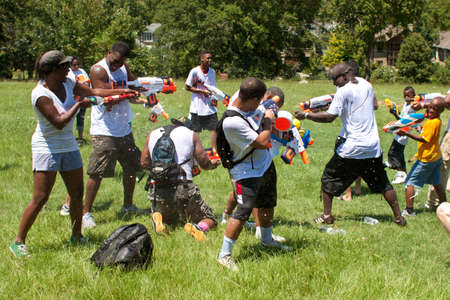 Atlanta, GA, USA - July 28, 2012:  Several unidentified people participate in a group squirt gun battle called the Fight4Atlanta, a fun water gun fight between dozens of local residents at Atlanta's Freedom Park.  The event was free and open to the public Stock Photo - 15621450