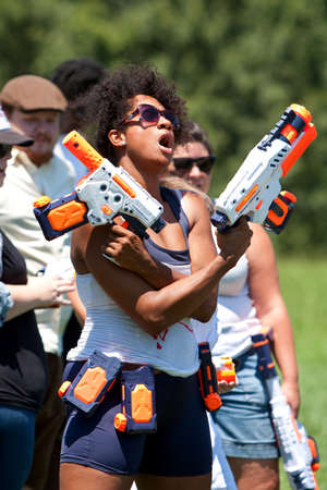 Atlanta, GA, USA - July 28, 2012:  An unidentifed woman defiantly raises her weapons just before the start of Fight4Atlanta, a fun water gun fight between dozens of local residents at Atlantas Freedom Park.