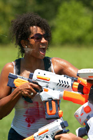 woman squirt: Atlanta, GA, USA - July 28, 2012:  An unidentified woman participates in a group water gun battle called the Fight4Atlanta, a fun squirt gun fight between dozens of local residents at Atlantas Freedom Park.  The event was free and open to the public.