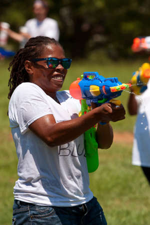 Atlanta, GA, USA - July 28, 2012:  An unidentified woman participates in a huge water gun battle called the Fight4Atlanta, a fun water gun fight between dozens of local residents at Atlanta's Freedom Park.  The event was free and open to the public. Stock Photo - 15621443