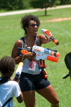 Atlanta, GA, USA - July 28, 2012:  An unidentified woman participates in Fight4Atlanta, a fun water gun fight between dozens of local residents at Atlanta's Freedom Park. Stock Photo - 15621434