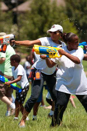 woman squirt: Atlanta, GA, USA - July 28, 2012:  Unidentified woman participate in a group water gun battle called the Fight4Atlanta, a fun squirt gun fight between dozens of local residents at Atlantas Freedom Park.  The event was free and open to the public.