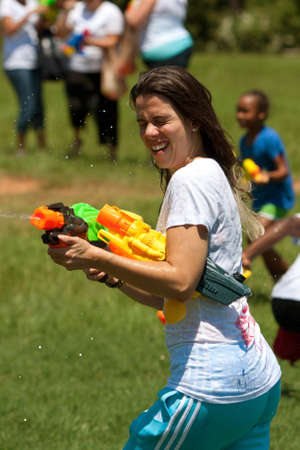 Atlanta, GA, USA - July 28, 2012:  Anl unidentified young woman participates in a huge water gun battle called the Fight4Atlanta, a fun water gun fight between dozens of local residents at Atlanta's Freedom Park.  The event was free and open to the public Stock Photo - 15621439