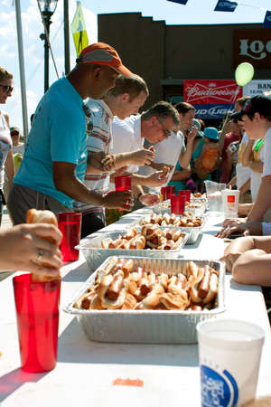 Tucker, GA, USA - July 28, 2012:  Contestants shove hot dogs into their mouths as they compete in a hot dog eating contest at the Tucker Summer Festival in downtown Tucker. The event was free and open to the public. Editorial