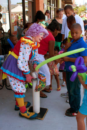 Tucker, GA, USA - July 28, 2012:  A female clown inflates a balloon for a child at the Tucker Summer Festival in downtown Tucker.  The event was free and open to the public.
