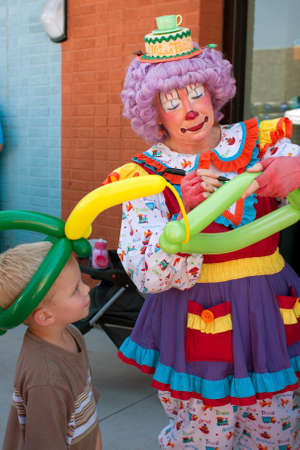tucker: Tucker, GA, USA - July 28, 2012:  A female clown makes a balloon hat for a child at the Tucker Summer Festival in downtown Tucker.  The event was free and open to the public. Editorial