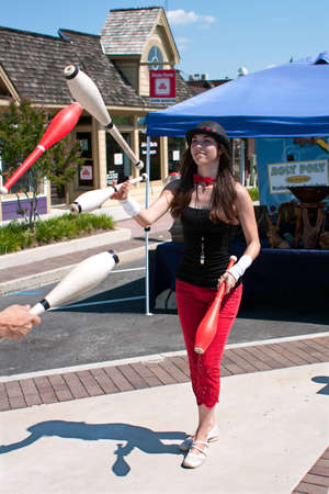 Tucker, GA, USA - July 28, 2012:  A female juggler juggles pins with a partner while performing at the Tucker Summer Festival in downtown Tucker. The event was free and open to the public.