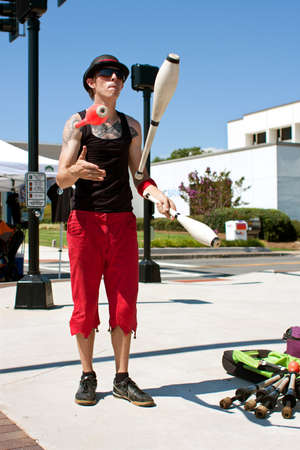 tucker: Tucker, GA, USA - July 28, 2012:  A male juggler juggles pins while performing at the Tucker Summer Festival in downtown Tucker. The event was free and open to the public. Editorial
