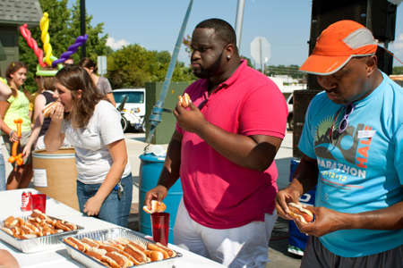 perro comiendo: Tucker, GA, EE.UU. - 28 de julio de 2012: Tres concursantes empuj�n perros calientes en la boca, ya que compiten en un concurso de comer perros calientes en el Festival de Verano en el centro de Tucker Tucker. El evento fue gratuito y abierto al p�blico.
