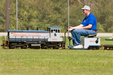 Conyers, GA, USA - August 25, 2012:  An unidentified man operates a miniature steam engine ride for kids at a wildlife festival held at the Georgia International Horse Park.