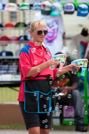 midway: Lawrenceville, GA, USA - September 15, 2012:  An unidentified female carnival worker uses bubble guns to blow bubbles to attract customers at the Gwinnett County Fair.