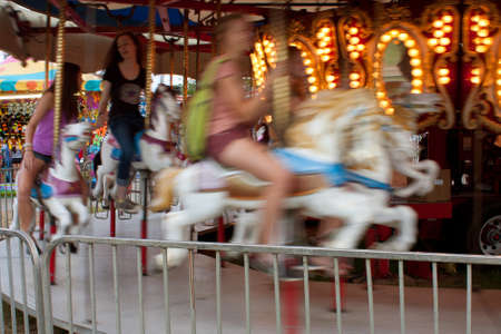 Lawrenceville, GA, USA - September 15, 2012:  Unidentified teenagers enjoy a ride on the merry-go-round on the midway at the Gwinnett County Fair.