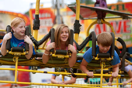 Lawrenceville, GA, USA - September 15, 2012:  Unidentified teenagers enjoy a speedy carnival ride on the midway at the Gwinnett County Fair.