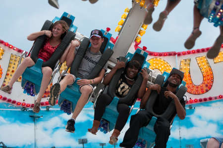 Lawrenceville, GA, USA - September 15, 2012:  Unidentified teenagers laugh on a scary carnival ride on the midway at the Gwinnett County Fair.