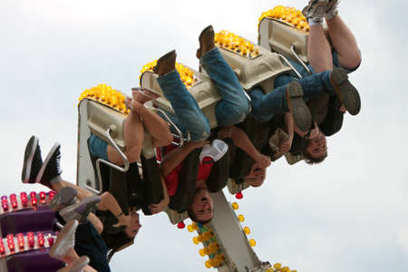 Lawrenceville, GA, USA - September 15, 2012:  Unidentified teenagers enjoy a scary carnival ride while upside down, on the midway at the Gwinnett County Fair.