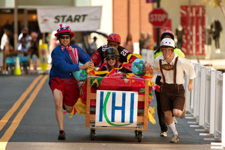 Atlanta, GA, USA - October 13, 2012:  Unidentified people in costumes push their teams bed down a street as they race in the Atlanta Mattress 500, a fundraiser bed race for the Atlanta Furniture Bank.