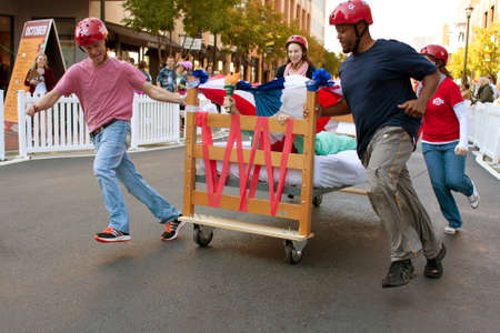 Atlanta, GA, USA - October 13, 2012:  Unidentified people push their teams bed through a turn as they race in the Atlanta Mattress 500, a fundraiser bed race for the Atlanta Furniture Bank.