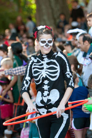 Atlanta, GA, USA - October 20, 2012:  A female in a skeleton costume performs with a hula hoop at the Little Five Points Halloween parade, as spectators look on. The L5P Halloween parade is one of the largest in the southeast. Editorial