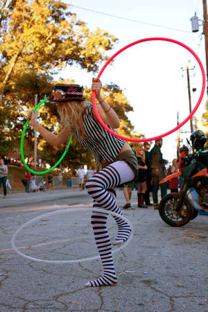 Atlanta, GA, USA - October 20, 2012:  An unidentified female performs with three hula hoops at once, as the crowed disperses from watching the Little Five Points Halloween parade. The L5P Halloween parade is one of the largest in the southeast.