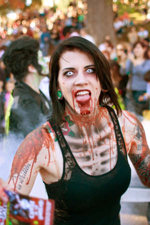Atlanta, GA, USA - October 20, 2012:  A female zombie makes a scary face as she walks in the Little Five Points Halloween parade, as spectators look on. The L5P Halloween parade is one of the largest in the southeast. Editorial