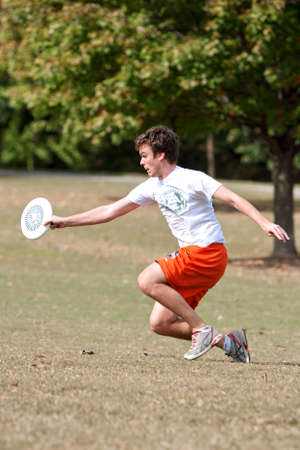 Atlanta, GA USA - October 27, 2012:  An unidentified young male reaches to catch a frisbee during an Ultimate Frisbee game between two teams in Piedmont Park. Editorial
