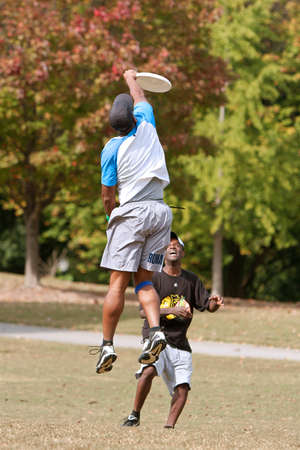 ultimate: Atlanta, GA USA - October 27, 2012:  An unidentified young male jumps to catch a frisbee during an Ultimate Frisbee game between two teams in Piedmont Park. Editorial