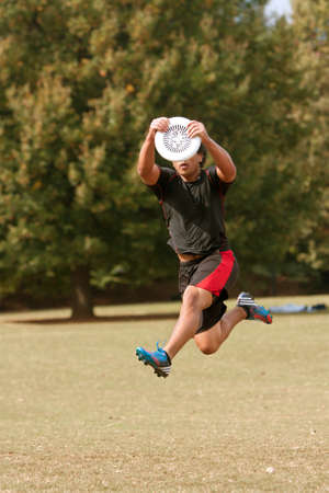Atlanta, GA USA - October 27, 2012:  An unidentified young male jumps to catch a frisbee during an Ultimate Frisbee game between two teams in Piedmont Park. Editorial