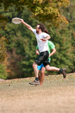 ultimate: Atlanta, GA, USA - October 27, 2012:  An unidentified man jumps to catch a frisbee during an Ultimate Frisbee game between two teams in Piedmont Park.